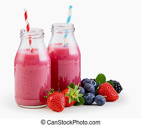 Fresh liquidised berry smoothies in glass bottles with strawberries, blueberries and blackberries alongside isolated on white with copy space
