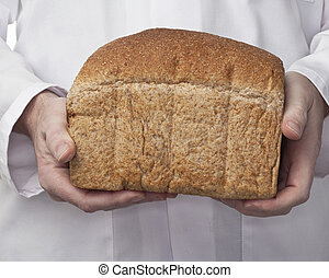 A freshly baked loaf of wholemeal brown bread being held by the baker