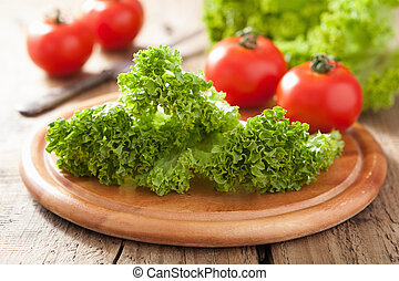 fresh lollo leaves and tomatoes on chopping board for salad
