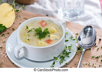 Fresh made Potatoe Soup in a bowl with herbs