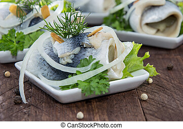 Fresh made Rollmop on a plate against wooden background