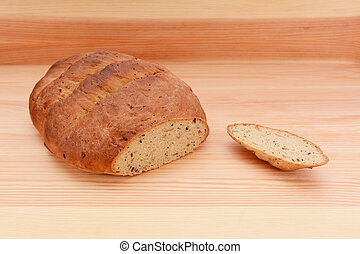 Fresh multi seed malted bread loaf with the crust cut off on a wooden surface