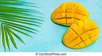Fresh mango organic product on a palm leaf. Blue background. Copy space. Top view.
