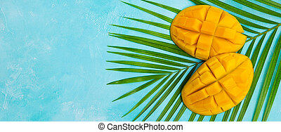 Fresh mango organic product on a palm leaf. Blue background. Top view. Copy space.