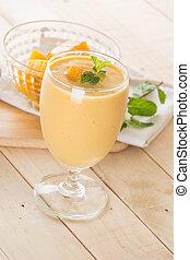 mango smoothie - fresh mango smoothie on wood background