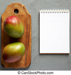 Fresh mangoes on a rustic wooden board, blank notebook over...
