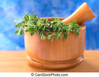 Fresh marjoram in wooden mortar with wooden pestle with a blue background (Selective Focus, Focus on the leaves in the front)