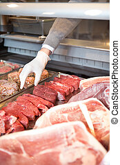 Fresh Meat Counter - Hand of assistant picking meat in the ...