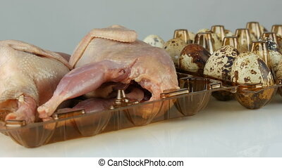 Fresh meat of quail in a plastic brown tray next to the...