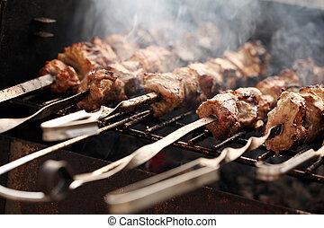 Fresh meat on a steel skewer in a smoke at brazier