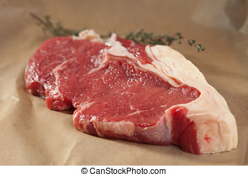 Fresh meat on wrapping paper - Big red beef steak on brown ...