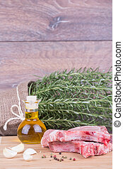 Fresh meat with rosemary on wooden background