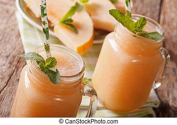 Fresh melon juice with mint macro in a glass jar. horizontal...