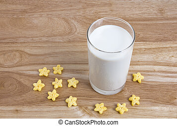 Fresh milk in glass with star cereals on the wooden table