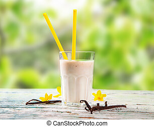 Fresh milk, vanilla drink on wooden table, assorted protein cocktail with nature background. Healthy lifestyle.