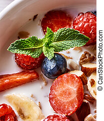 Fresh milk with homemade honey granola and natural organic ingredients - berries, nuts and mint in the white ceramic bowl. Close-up.