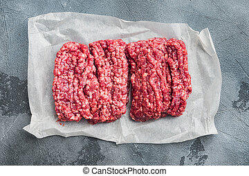 Fresh minced meat ground beef, on gray background, top view flat lay