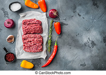 Fresh minced meat ground beef, on gray background, top view flat lay with copy space for text