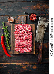 Fresh minced meat ground beef, on old dark wooden table background, top view flat lay