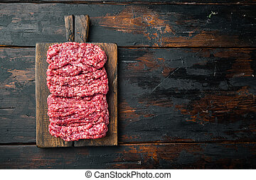 Fresh minced meat ground beef, on old dark wooden table background, top view flat lay with copy space for text