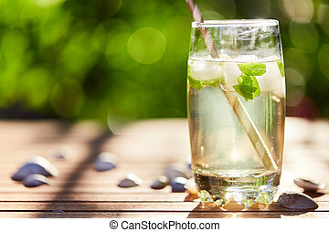 Fresh mint drink with ice in a glass on  a wooden table