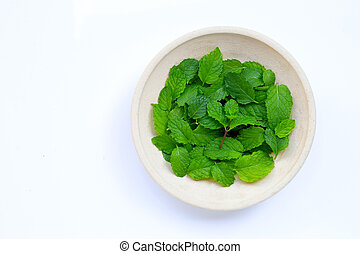 Fresh mint leaves in pottery plate on white background.