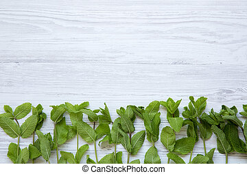 Fresh mint on white wooden background, top view. Copy space.