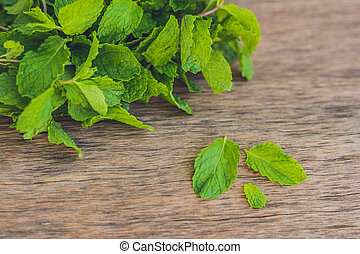 Fresh mint on wooden table copy space. Selective focus