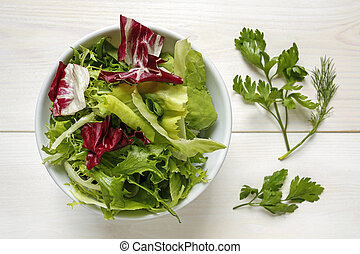 fresh mixed lettuce leaves in a bowl on white background