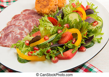 Fresh mixed vegetable salad and sliced sausage