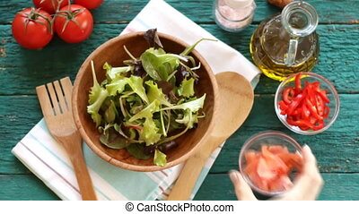 Fresh mixed vegetables falling into bowl of salad . Slow motion