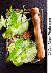 Fresh mojito drinks on stone surface