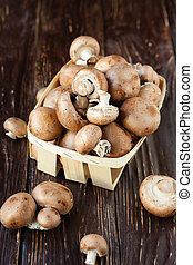 fresh mushrooms, in a basket on the boards