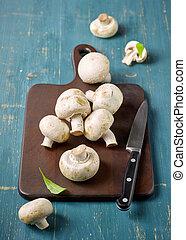 fresh mushrooms on wooden cutting board