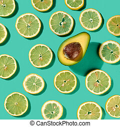 Summer fruits citrus lemon slices pattern with half of avocado with shadows on a light green background. Concept of healthy dieting food. Top view.