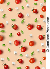 Vegetable pattern from freshly picked natural organic ripe healthy tomatoes cherry, basil leaves and cheese cubes on a beige background. Top view.