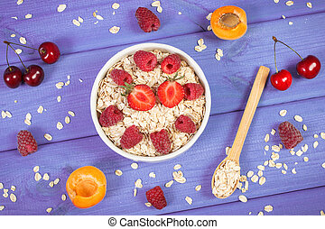 Fresh oatmeal with fruits and flakes on spoon, healthy lifestyle and nutrition