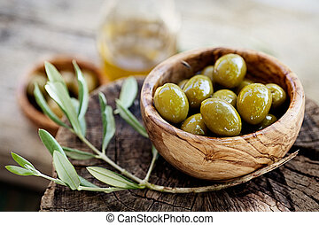 Fresh olives and olive oil on rustic wooden background. ...