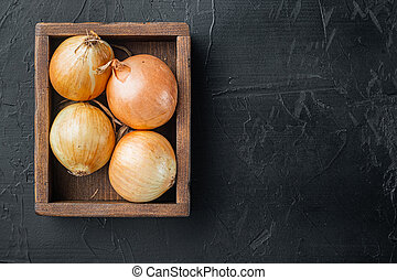 Fresh onions harvest, on black background, top view flat lay with copy space for text