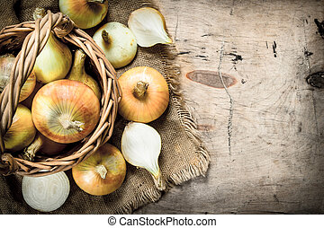 Fresh onions in a basket. On wooden background.