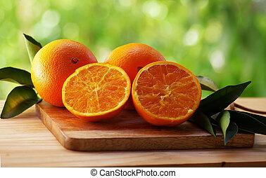 fresh orange fruit with leaf  on green background