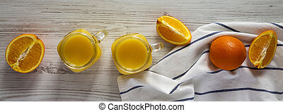 Fresh orange juice in glass jars on a white wooden background, top view. Flat lay, from above, overhead.