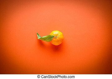 Fresh orange mandarin with leaves, on an orange background, flat lay.