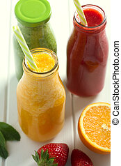 Fresh orange, strawberry and broccoli smoothie in bottles with fruits and vegetables on a white wooden rustic background, closeup shot.