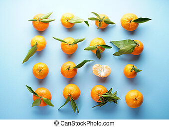 Fresh orange tangerines with green leaves, on a blue background. Flat lay.