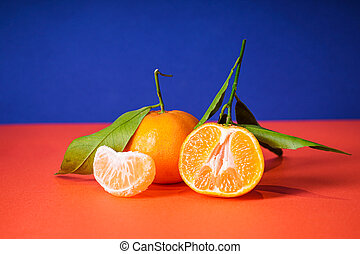 Fresh orange tangerines with leaves, on a blue background. Close-up.