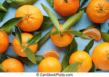 Fresh orange tangerines with leaves, on a blue background. Flat lay.
