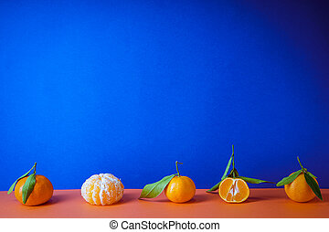 Fresh orange tangerines with leaves, on a blue background, place for text.