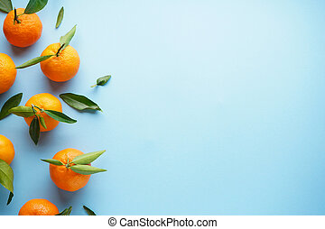 Fresh orange tangerines with leaves, on a blue background. Place for text.