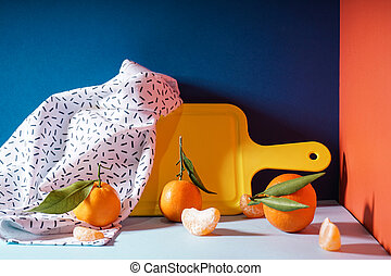 Fresh orange tangerines with leaves with a yellow cutting board and a towel, on a colorful background